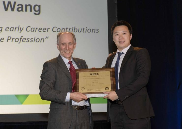 Hua Wang is presented with the 2017 IEEE MTT-S Outstanding Young Engineer Award by Dylan Williams, the president of IEEE MTT-S.